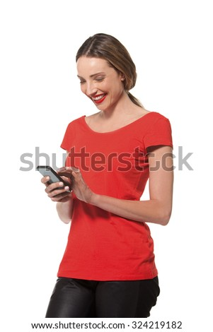 Young woman in red text messaging on smart phone - stock photo