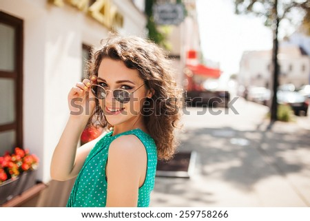 Young woman in round sunglasses and dress with curly hair smiling over the shoulder in the city street - stock photo