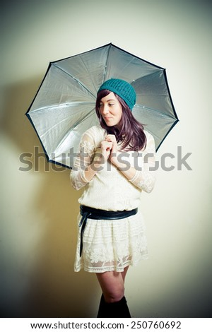 Young woman in 70s hippie style posing looking down with umbrella vintage color effect - stock photo