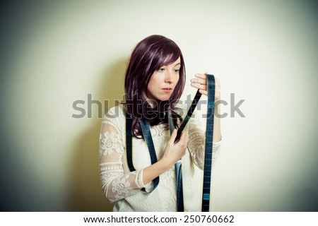 Young woman in 70s hippie style watching 35mm movie film vintage color effect - stock photo