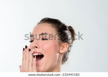 Young woman in 20s yawning with happy face expression. Isolated on white with copyspace. - stock photo