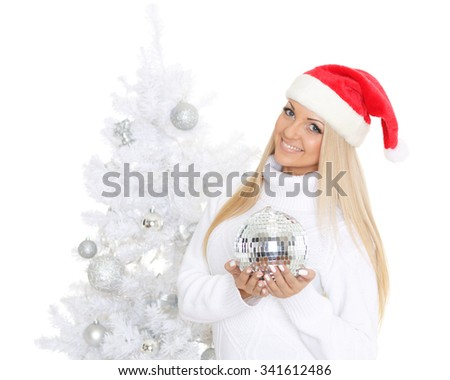 Young woman in Santa Claus cap  with mirror ball stands near Christmas tree on a white background. - stock photo