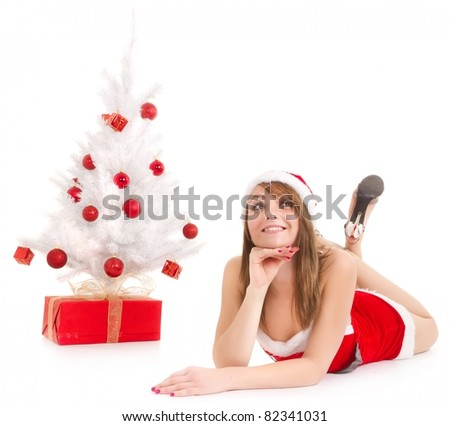 young woman in santa suit lying near christmas tree and gift