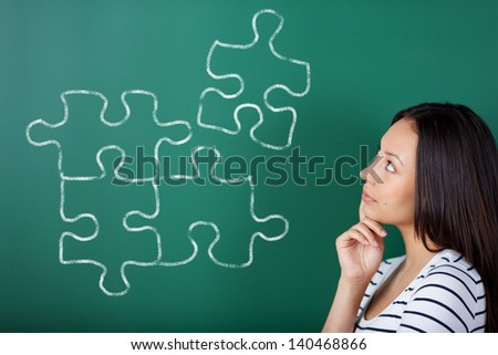 young woman in school completing puzzle on blackboard