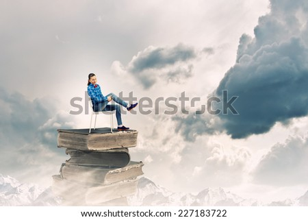 Young woman in shirt sitting in chair on pile of books - stock photo