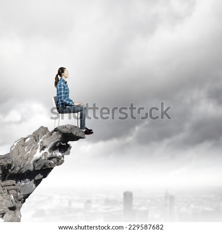 Young woman in shirt sitting in chair on rock top - stock photo