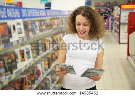 young woman in shop chooses disk - stock photo