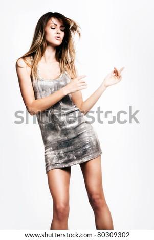 young woman in short dress dancing, studio shot - stock photo