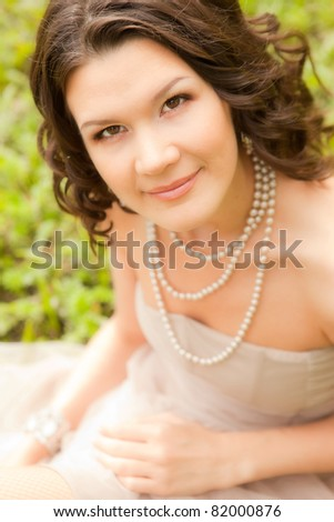 young woman in short dress sit on grass - stock photo