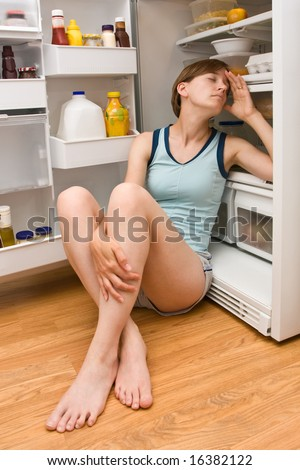Young woman in shorts and tank top sitting next to open refrigerator to cool off.