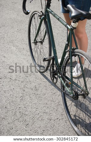 young woman in shorts near the city bike fixed gear selective focus - stock photo
