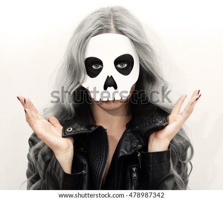 young woman in skull mask face of a young woman in paper halloween mask