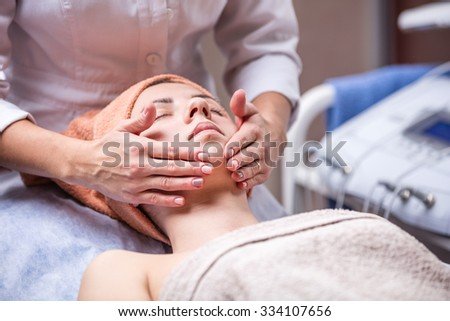 Young woman in spa salon, beautician performing facial massage - stock photo