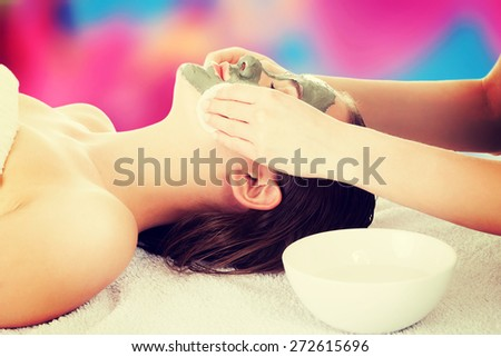 Young woman in spa with a mask on her face - stock photo
