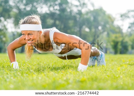 Young woman in sport wear doing push ups in park - stock photo