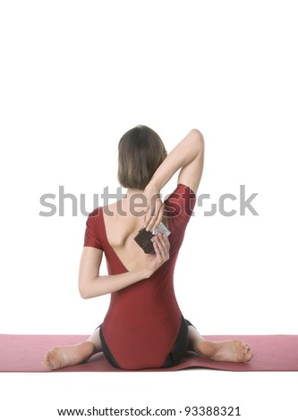 Young woman in sports clothes trying to hide a chocolate bar behind her back - stock photo