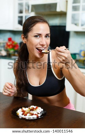 Young woman in sportswear sits in the house kitchen before plate with nutritional supplements. - stock photo