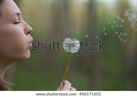 Young woman in spring or summer blowing dandelion flower enjoying nature - stock photo