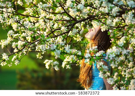 Young woman in spring orchard - stock photo