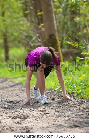 Young woman in starting position to go running - stock photo