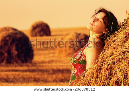Young woman in straw field with bales. Day dreaming with closed eyes. - stock photo