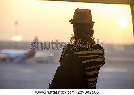 Young woman in straw hat and summer dress with backpack waiting for flight in modern airport terminal building, watching airplanes in window on sunrise or sunset, back view - stock photo