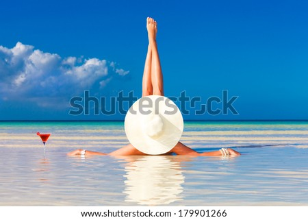 young woman in straw hat laying at the tropical beach and enjoying cocktail  - stock photo