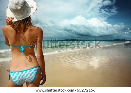 Young woman in straw hat standing on a sand near sea and looking to a horizon - stock photo