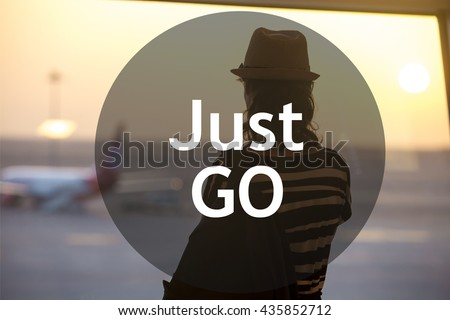 "Young woman in straw hat waiting for flight in modern airport terminal building. Watching airplanes in window on sunrise or sunset. Rear view with motivational text ""Just go"""