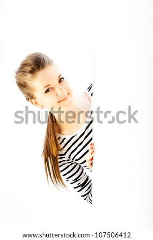 Young woman in striped vest looking out the corner - stock photo