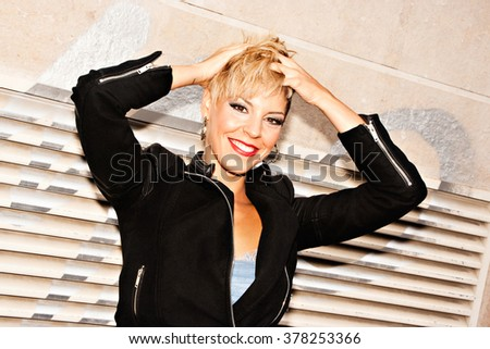 Young woman in style of urban fashion. Short blonde hairstyle. Dressed with motorcycle black jacket and a blue dress. Urban fashion photography. Horizontal image.