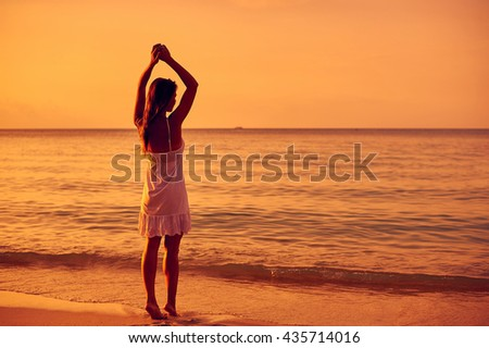 Young woman in summer dress enjoying freedom, standing on a ocean shore with hands raised  - stock photo