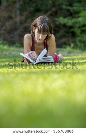 Young woman in summer dress lying in a green grass reading a book or novel. - stock photo