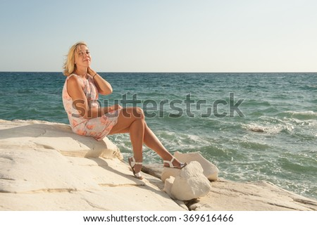 Young woman in summer dress sitting on the rocks by the sea
