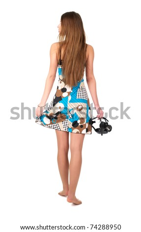 Young woman in summer dress with her shoes in hand against white background - stock photo
