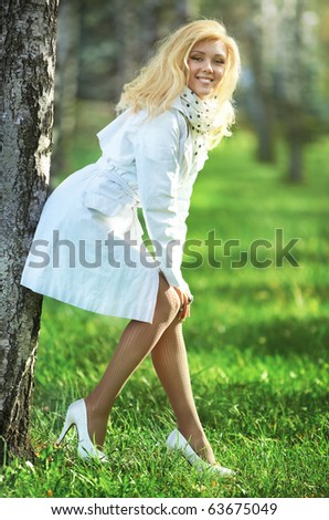 Young woman in summer park. Brigth soft colors. - stock photo