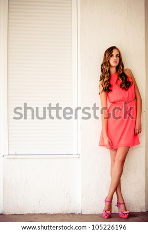 young woman in summer short dress lean on white wall outdoor shot day time - stock photo