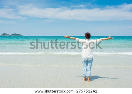 Young woman in summer standing on beach and looking to the sea - stock photo
