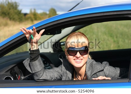 Young woman in sun-glasses is siting in her car with key from it. She is smiling happy - stock photo