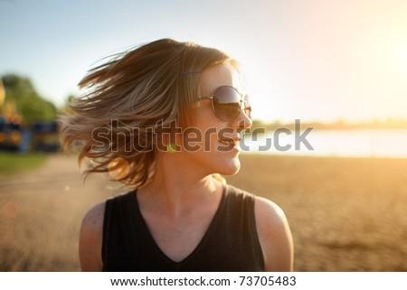 Young woman in sunglasses enjoying summer breeze at sunset beach. Closeup, shallow DOF. - stock photo