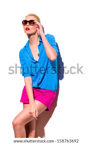 Young woman in sunglasses is leaning on the wall and looking away Three quarter length studio shot isolated on white. - stock photo