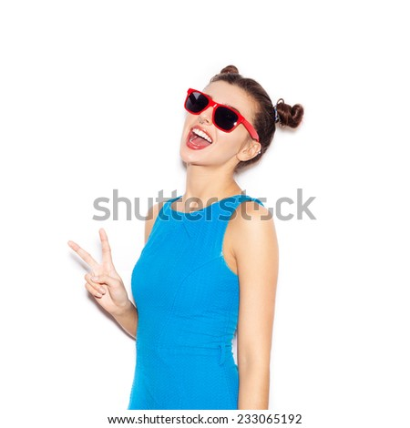 Young woman in sunglasses  laughing. Beauty girl with bright makeup hairstyle with horns in a blue dress having fun. On a white background, not isolated - stock photo