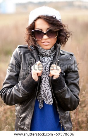 Young woman in sunglasses standing in the field - stock photo