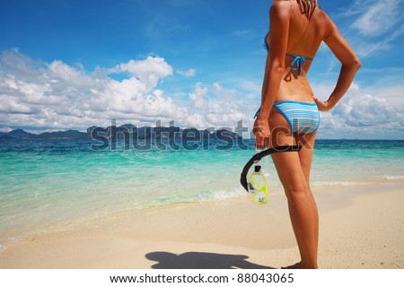 Young woman in swim suit standing on a beach and holding a snorkel and mask - stock photo