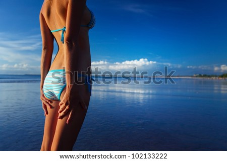 Young woman in swim suit standing relaxing on a tropical beach