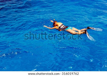 Young woman in swimsuit snorkeling in blue and transparent tropical sea - stock photo