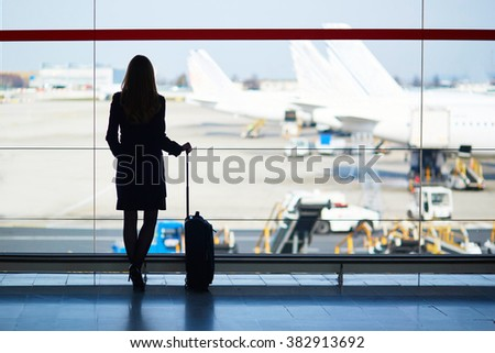 Young woman in the airport, looking through the window at planes - stock photo