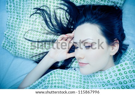 Young woman in the bed in bright light