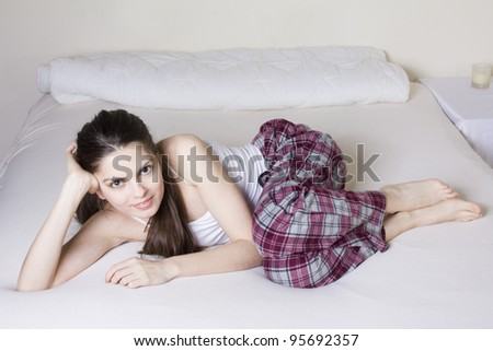 Young woman in the bed, in lila pijama and white top