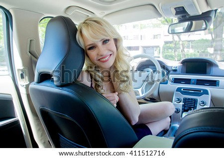 young woman in the car driver seat having fun